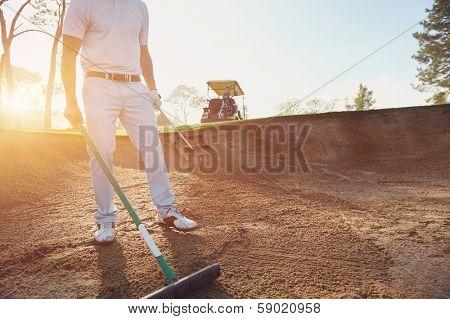 Golfer raking bunker in early morning with sunrise
