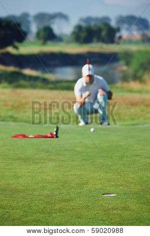Golfer aiming lining up putt on green poster