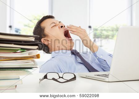 Exhausted Young Businessman Yawning At Work