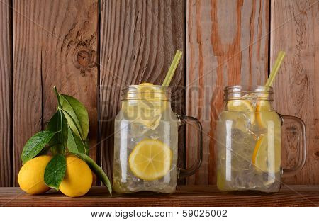 Glasses of lemonade  and lemons on a ledge in front of a rustic wooden kitchen wall. The mason jar style glasses have handles and drinking straws.
