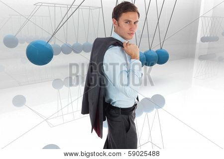 Serious businessman holding his jacket against blue newtons cradle