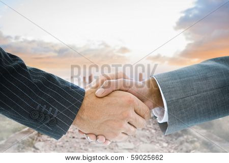 Composite image of business handshake against stony path leading to misty city horizon poster