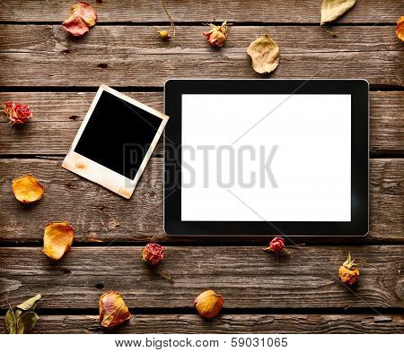Digital tablet computer with blank instant photo and rose petals on old wooden desk.