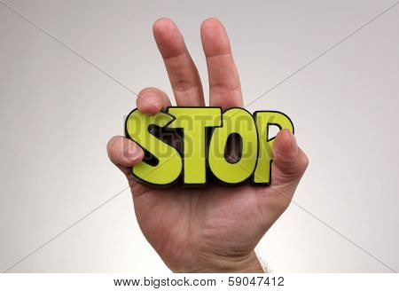 Stop gesture with hand holding stop sign