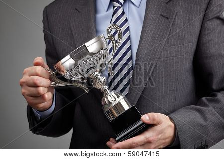Businessman celebrating with trophy award for success in business or first place sporting championship win poster
