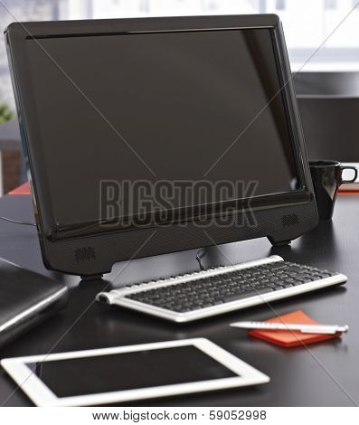 Closeup photo of office desk with computer and tablet pc.