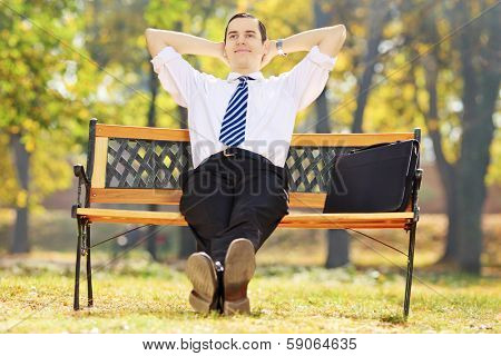 Relaxed young businessman sitting on a wooden bench in a park