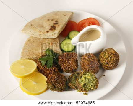 Homemade falafels (herbed and spicy chickpea balls) on a plate with Egyptian flat bread, lemon slices, tomato, cucumber and a tahina sauce. poster