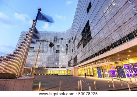European comission building in dusk with flags waving