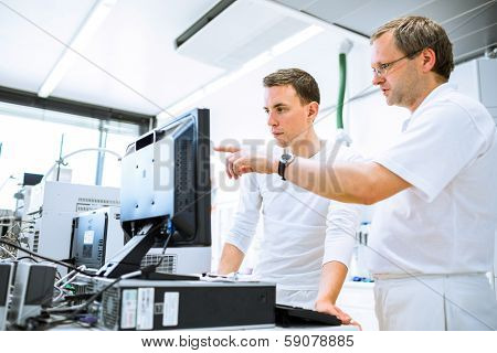 Team of researchers carrying out experiments in a lab (shallow DOF; color toned image)
