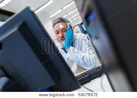 Senior male researcher carrying out scientific research in a lab - dozing off for a while in a funny way (shallow DOF; color toned image)
