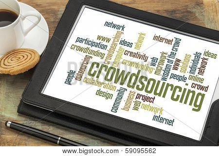 crowdsourcing word cloud on a  digital tablet with a cup of coffee