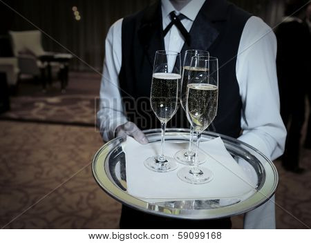 Waiter welcomes guests with champagne