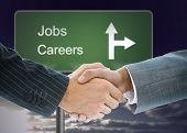 Composite image of business handshake against signpost showing the direction of jobs and careers poster