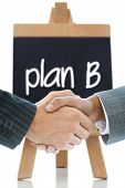 Composite image of business handshake against plan b written on a chalkboard poster
