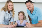 Portrait of happy parents assisting cute girl in using digital tablet at table in kitchen poster