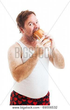 Middle aged man in his underwear, stuffing his face with a giant hoagie sandwich.  Isolated on white.