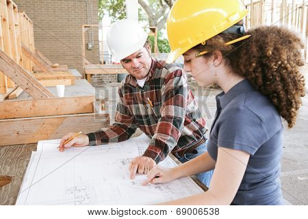Vocational education student learning to read construction blueprints.