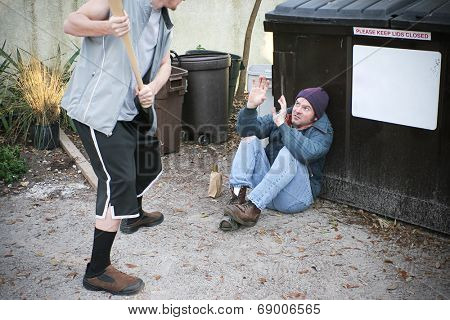 Young thug male threatening to beat a homeless man with a baseball bat.