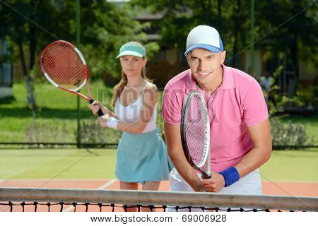 Young male and female tennis players while playing tennis on the tennis court poster