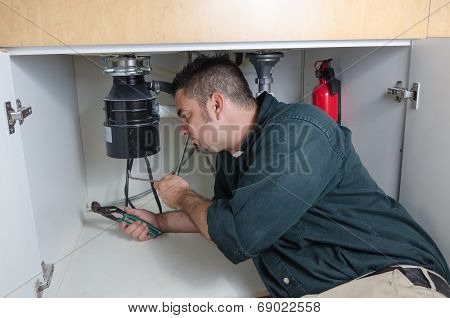Plumber Fixing A Garbage Disposal