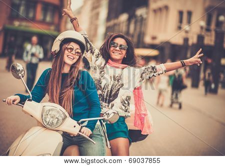 Multi ethnic girls on a scooter in european city