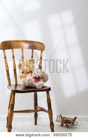 Two teddy bears sitting on a chair with sunlight streaming through