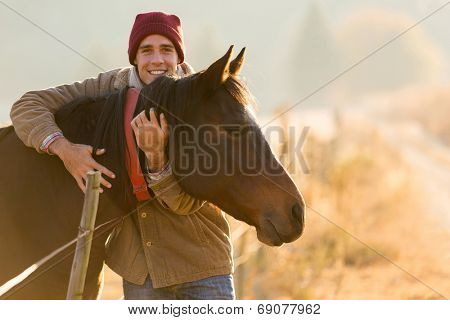 portrait of happy man hugging his horse in the ranch