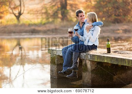 happy young couple drinking red wine by the lake