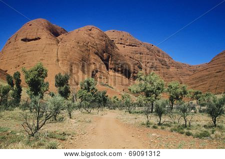 Dirt track leading towards rock formation