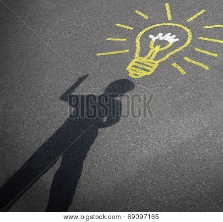 Childhood imagination and child creativity concept as the shadow of an inspired boy with a lightbulb chalk drawing on city asphalt as a symbol of inspiration and creative learning or back to school ideas. poster