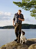 The hunter trains his English Springer Spaniel puppy on the shore poster