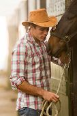 young cowboy whispering to a horse in stable poster