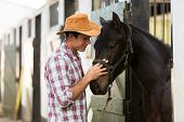 young horse breeder comforting a horse in stable poster