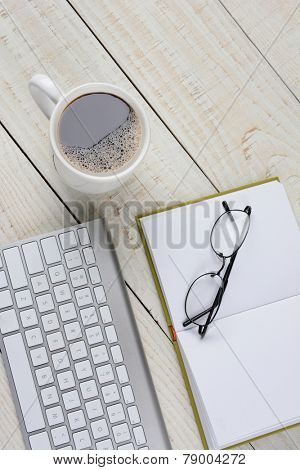 Vertical overhead shot of a home office desk with a cup of coffee, and open book with glasses, and a computer keyboard. The items are on a rustic white washed desk with copy space.