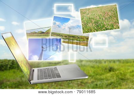 Laptop and images of nature on field and sky background