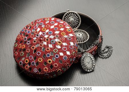 Old indian jewelery box with the earrings and pendant on a wooden background.