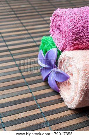 Spa towels rolls and flower lying on wooden mat. Space for your text. Vertical composition.