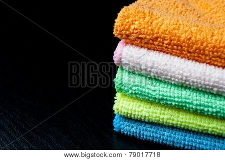 Closeup stack of colorful towels on a black wood. Space for your text.