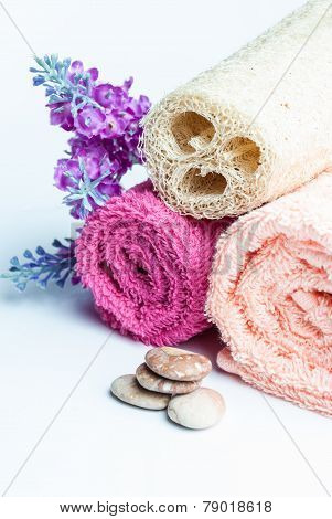 Spa towels rolls flower and stones lying on shite background. Space for your text. Vertical composition.