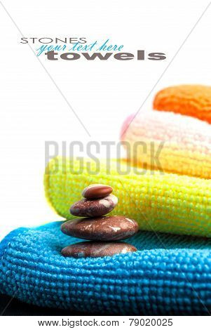 Closeup stack of colorful towels and stones on white background. Space for your text. ** Note: Shallow depth of field