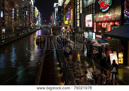 OSAKA, JAPAN - 30 NOVEMBER 2014: People line up outside a restaurant besides a river in Osaka. The vibrant nightlife is a tourist attraction in this second largest city in Japan.
