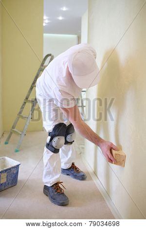 Builder polishing the wall using a sanding sponge