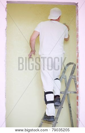 Builder standing on a ladder and inflict plaster on wall, view through doorway