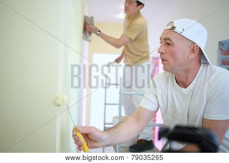 Two builders making finish in the apartment