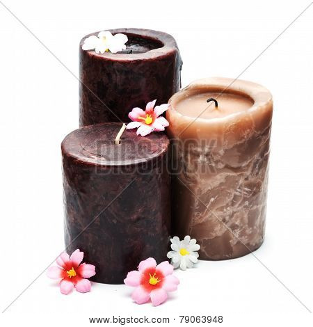 Three thick candles with flowers isolated on white.