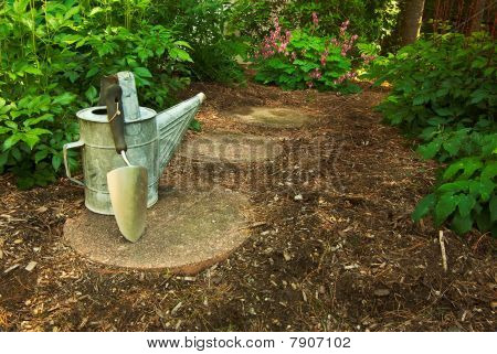 An Old Watering Can And Trowel Sit On A Garden Path In The Woods