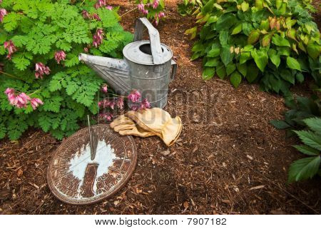 Sundial On Bark Mulch With Garden Gloves And Worn Watering Can