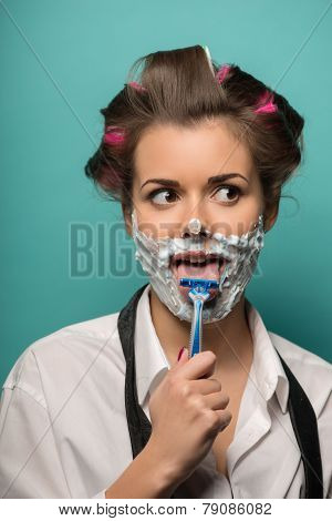 Cute brunette woman in hair curlers posing with foam on face sha