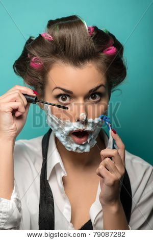Cute brunette in hair curlers and foam posing with razor on blue